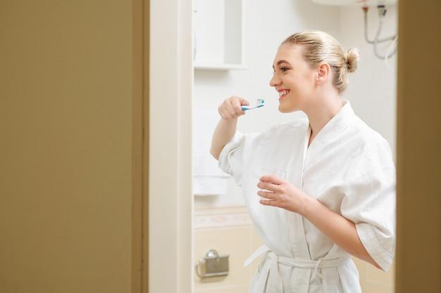 Szczęśliwa kobieta szczotkuje zęby