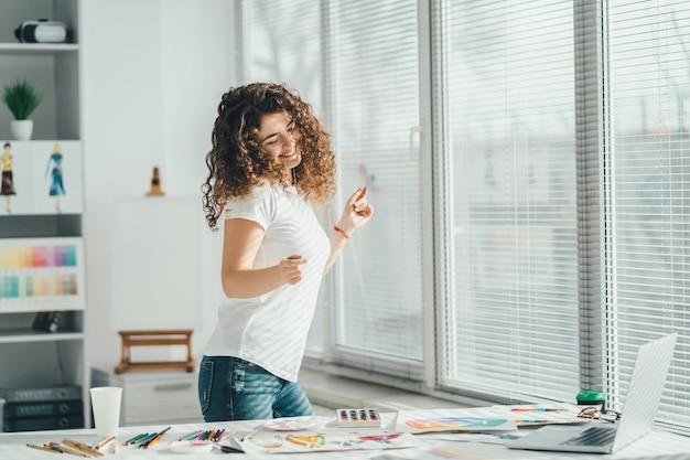 Szczęśliwa kobieta tańcząca przy stole ze zdjęciami