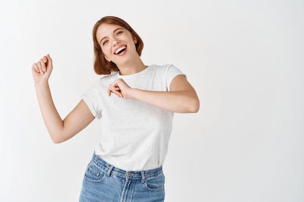 Szczęśliwa kobieta tańczy i bawi się, śmiejąc się radośnie, stojąc przy białej ścianie