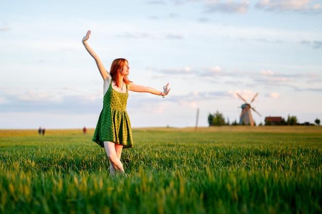 Szczęśliwa kobieta tańczy w polu pełnym żółtych kwiatów