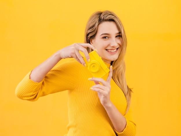 Szczęśliwa kobieta trzyma aparat