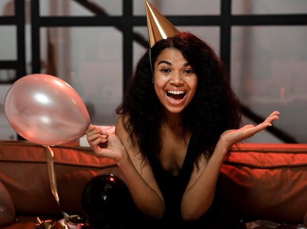 Szczęśliwa kobieta trzyma balon na imprezie sylwestrowej