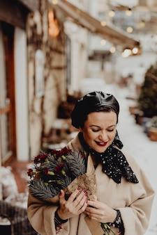 Szczęśliwa kobieta trzyma bukiet kwiatów w okresie zimowym