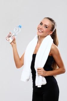Szczęśliwa kobieta trzyma butelkę woda