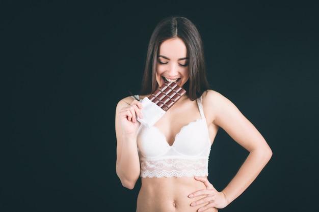 Szczęśliwa kobieta trzyma czekoladowego baru. młoda kobieta z długimi czarnymi włosami stoi na białym tle. dziewczyna ma sportową figurę, jest ubrana w białą bieliznę.