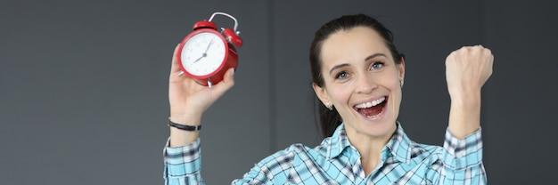Szczęśliwa kobieta trzyma czerwony budzik dostarczanie projektów biznesowych