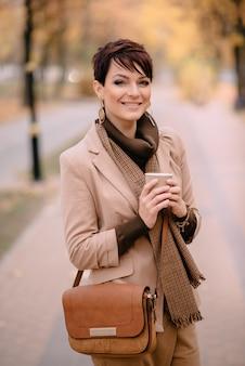 Szczęśliwa kobieta trzyma filiżankę kawy w ręce i ono uśmiecha się