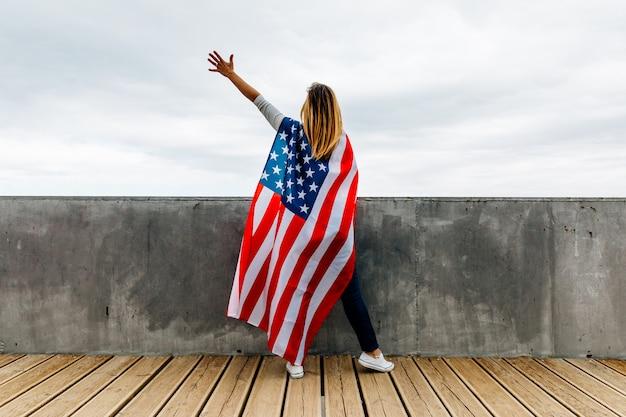 Szczęśliwa kobieta trzyma flaga amerykańską
