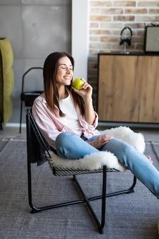 Szczęśliwa kobieta trzyma jabłka i szkła wodny obsiadanie na kanapie w żywym pokoju