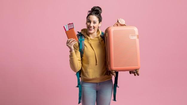 Szczęśliwa kobieta trzyma jej bagażu i samolotu bilet