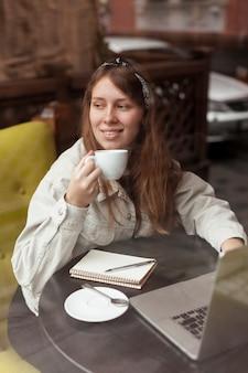 Szczęśliwa kobieta trzyma kawowego pobliskiego okno