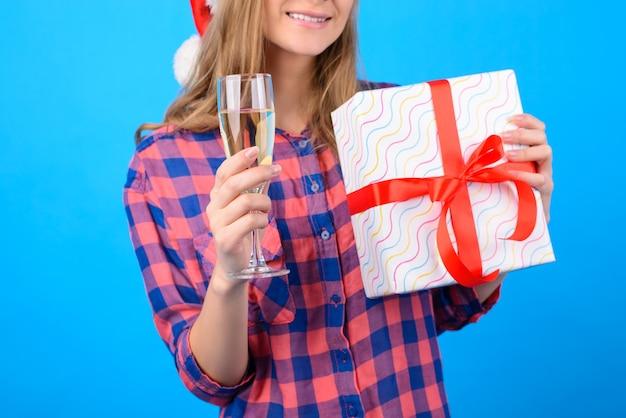 Szczęśliwa kobieta trzyma kieliszek szampana i pudełko z kokardą