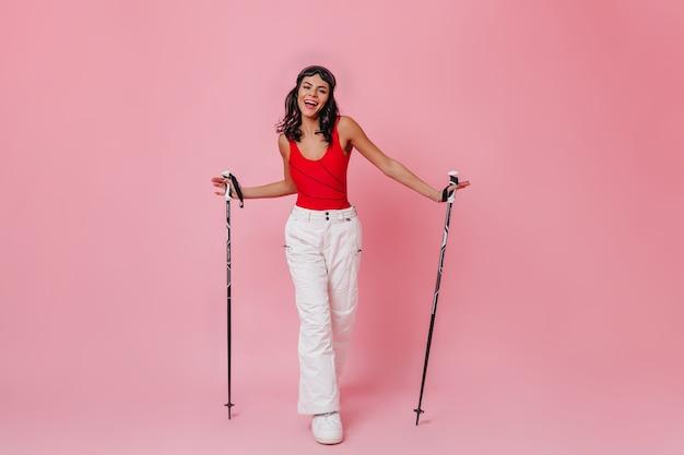 Szczęśliwa kobieta trzyma kijki narciarskie na różowym tle