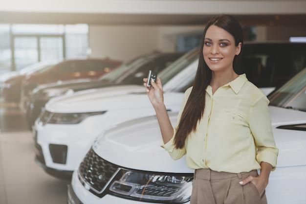 Szczęśliwa kobieta trzyma kluczyki do samochodu jej nowy samochód