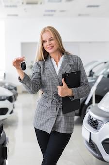 Szczęśliwa kobieta trzyma kluczyki do samochodu
