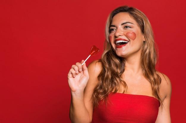Szczęśliwa kobieta trzyma lizaka