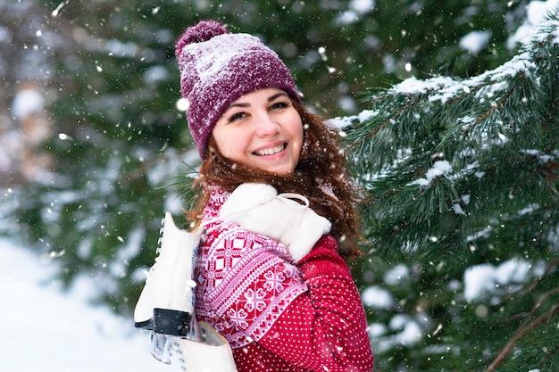 Szczęśliwa kobieta trzyma łyżwy zimowe na jej ramieniu. zajęcia zimowe i sport.