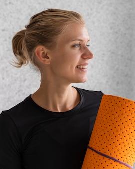 Szczęśliwa kobieta trzyma matę do jogi