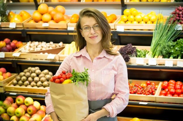 Szczęśliwa kobieta trzyma papierową torbę
