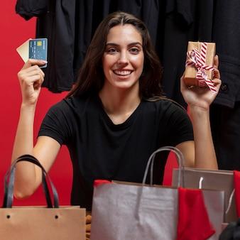 Szczęśliwa kobieta trzyma pieniądze i zapakowany prezent