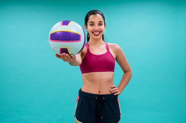 Szczęśliwa kobieta trzyma piłkę do siatkówki