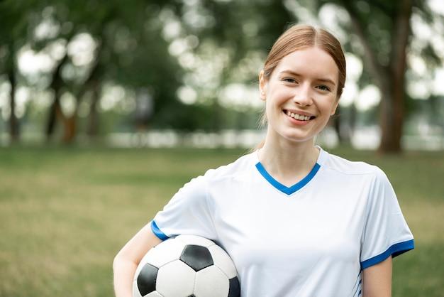 Szczęśliwa kobieta trzyma piłkę na zewnątrz