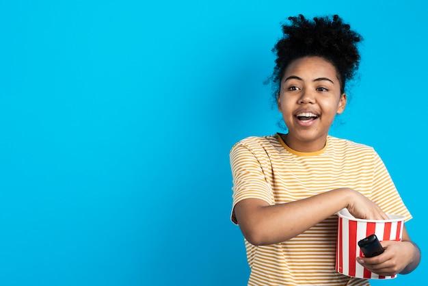 Szczęśliwa kobieta trzyma popcorn wiadro i pilot do tv