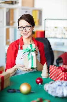 Szczęśliwa kobieta trzyma prezent na boże narodzenie lub prezent