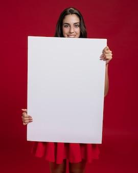 Szczęśliwa kobieta trzyma pustego sztandar