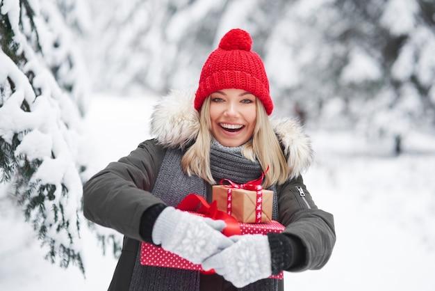 Szczęśliwa kobieta trzyma stos prezentów świątecznych