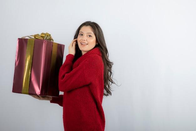 Szczęśliwa kobieta trzyma świąteczny prezent ze wstążką.