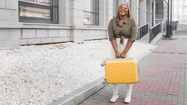 Szczęśliwa kobieta trzyma swój bagaż z miejsca na kopię