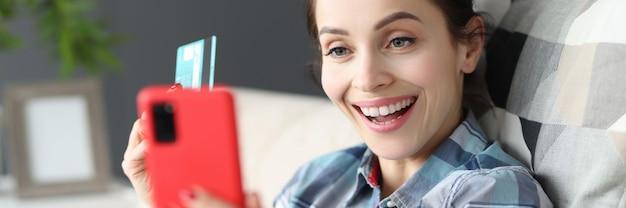 Szczęśliwa kobieta trzyma telefon komórkowy i kredytową kartę bankową sklep internetowy koncepcja