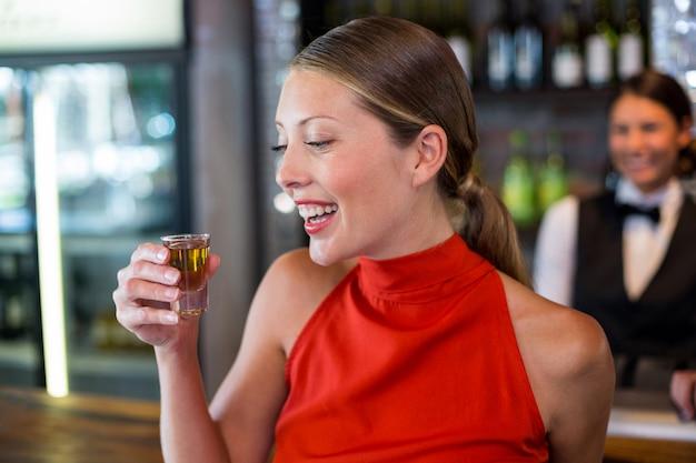 Szczęśliwa kobieta trzyma tequila strzał przed baru kontuarem