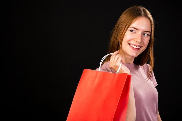 Szczęśliwa kobieta trzyma torba na zakupy patrzeje daleko od