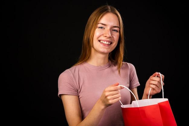 Szczęśliwa kobieta trzyma torba na zakupy