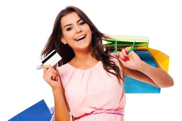 Szczęśliwa kobieta trzyma torbę na zakupy i kartę kredytową