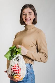Szczęśliwa kobieta trzyma torbę zakupów spożywczych wielokrotnego użytku
