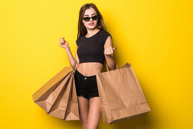 Szczęśliwa kobieta trzyma torby na zakupy na żółtej ścianie