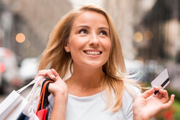 Szczęśliwa kobieta trzyma torby na zakupy w jednej ręce i kartę kredytową w drugiej