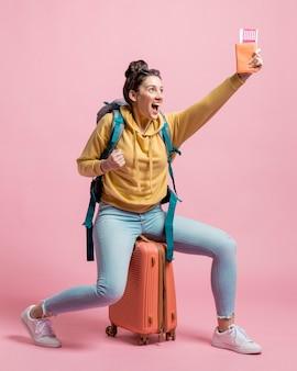 Szczęśliwa kobieta trzyma up jej paszport i samolotowi bilety