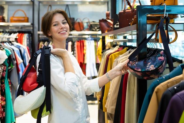 Szczęśliwa kobieta trzyma w rękach wiele toreb z paskiem