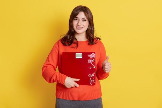 Szczęśliwa kobieta trzyma wagę na żółto, patrzy na aparat z przyjemnym spojrzeniem i wskazuje kciuk w górę, będąc zadowolona z jej wyniku odchudzania.