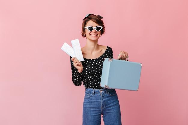 Szczęśliwa kobieta trzyma walizkę i bilety w okularach przeciwsłonecznych