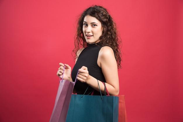 Szczęśliwa kobieta trzyma wiele toreb na czerwonym tle