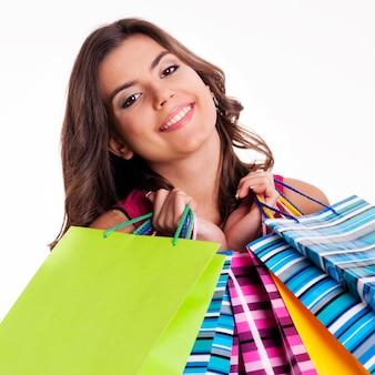 Szczęśliwa kobieta trzyma wielu kolorowych toreb na zakupy
