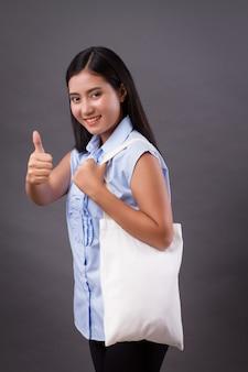 Szczęśliwa kobieta trzyma worek recyklingu, dając kciuk gest