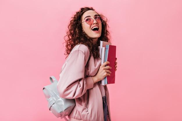 Szczęśliwa kobieta trzyma zeszyty i plecak
