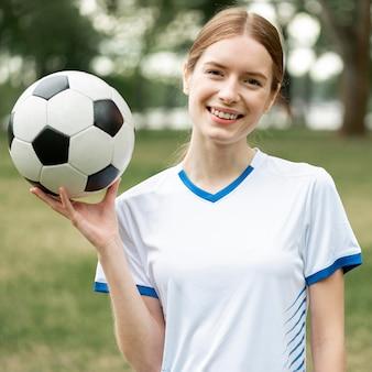 Szczęśliwa kobieta trzymając piłkę na zewnątrz