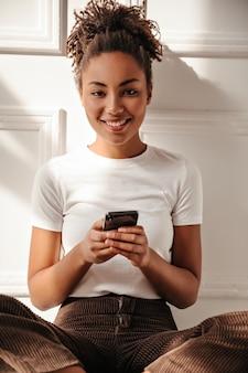 Szczęśliwa kobieta trzymając smartfon i patrząc z przodu